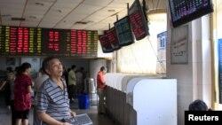 Nhà đầu tư nhìn vào bảng điện tử hiển thị thông tin chứng khoán tại một trung tâm giao dịch ở Thượng Hải.