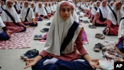 Siswi Muslim di India berlatih yoga di sekolah untuk perayaan Hari Yoga Internasional pertama di Ahmadabad, India (17/6). (AP/Ajit Solanki)