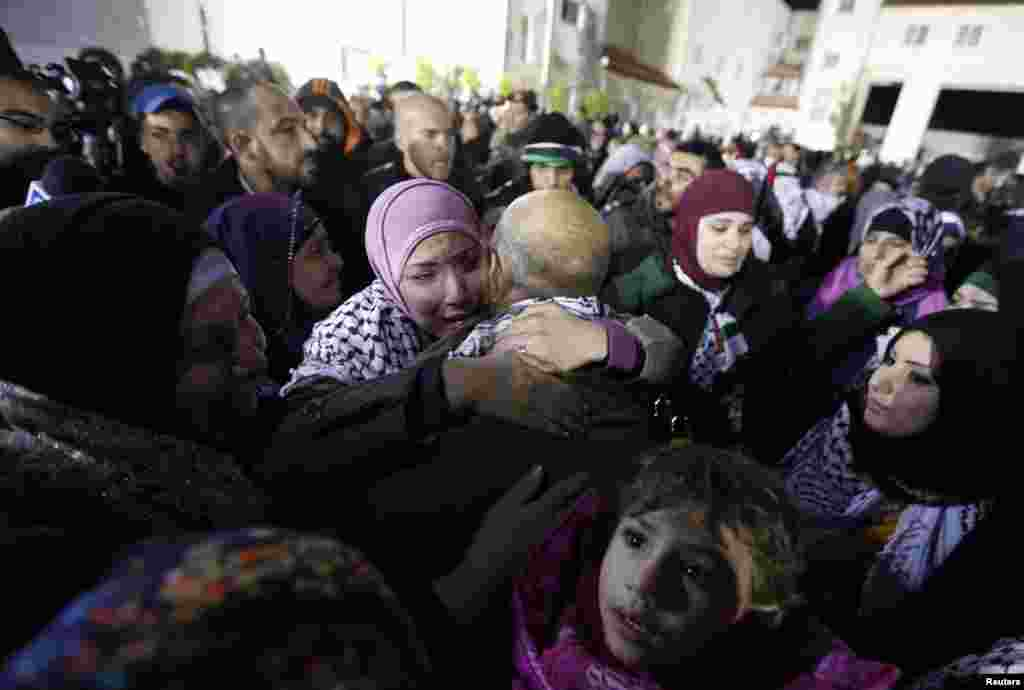 A prisoner released from an Israeli prison (C, back to camera) is welcomed by relatives in Ramallah, West Bank, Dec. 31, 2013.