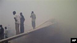 추락한 여객기의 꼬리 날개부분에 올라서서 사고 현장을 지켜보는 시민들