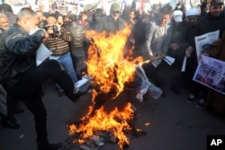 Followers of Shi'ite cleric Muqtada al-Sadr burn an effigy of King Salman of Saudi Arabia as they hold posters of Sheik Nimr al-Nimr during a demonstration in Baghdad, Iraq, Jan. 4, 2016.