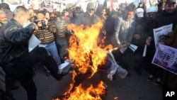 FILE - Followers of Shiite cleric Muqtada al-Sadr burn an effigy of King Salman of Saudi Arabia as they hold posters of Sheik Nimr al-Nimr during a demonstration in Baghdad, Iraq, Jan. 4, 2016.
