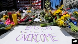 FILE - Flowers and signs adorn a barrier, two days after two explosions near the of finish line of the Boston Marathon at a makeshift memorial for victims and survivors, April 17, 2013.