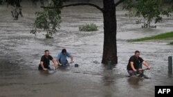 Orang-orang mengendarai sepeda melalui sebuah taman yang tergenang banjir di tepi sungai Nepean di pinggiran Penrith, saat kota Sydney, Australia, bersiap menghadapi banjir terburuk dalam beberapa dekade, Minggu 21/3. (Foto: AFP)
