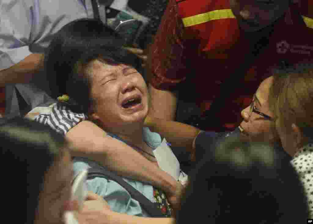 Gia đình của hành khách trên chuyến bay AirAsia 8501 òa khóc sau khi nhìn thấy những hình ảnh của các thi thể trôi nổi không mặc áo phao trên truyền hình, ngày 30/12/2014.