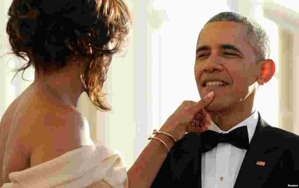 در حاشیه استقبال از سران کشورهای اروپایی، میشل اوباما از روی صورت همسرش، چیزی را پاک می کند.