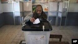 Seorang pria Mesir memasukkan surat suaranya untuk putaran kedua referendum konstitusi di sebuah TPS di Fayoum, sekitar 100 kilometersebelah selatan Kairo, Mesir, Sabtu (22/12).