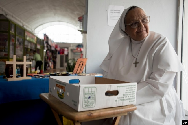 Sister Carmen Negrón, 64, sells handmade rosaries and religious icons in the Plaza del Mercado in San Juan, Puerto Rico, April 17, 2019. Negrón says she's noticed a drop in sales because of what seems to be fewer people in the area.