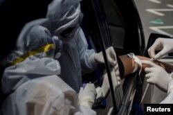Para petugas medis mengambil sampel darah dalam lantatur tes cepat di tengah wabah virus corona (COVID-19) di Bandung, Jawa Barat, 4 April 2020. (Foto: Antara via Reuters)