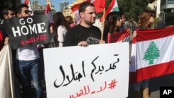 "FILE - Activists hold Lebanese flags and an Arabic placard, center, that reads:""Your extension is an occupation, no to the extension,"" during a protest against the extension of the Lebanese parliament, on a road that leads to the Parliament building, in downtown Beirut, Lebanon."
