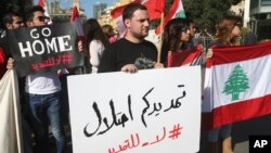 """FILE - Activists hold Lebanese flags and an Arabic placard, center, that reads:""""Your extension is an occupation, no to the extension,"""" during a protest against the extension of the Lebanese parliament, on a road that leads to the Parliament building, in downtown Beirut, Lebanon."""