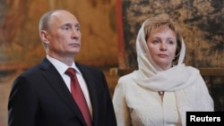 FILE - Vladimir Putin (L) is seen with his his then wife Lyudmila at a church service in Moscow, May 7, 2012.