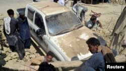 Warga setempat berusaha membersihkan kendaraan dari reruntuhan akibat gempa di distrik Awaran – propinsi Baluchistan, Pakistan barat daya (25/9).