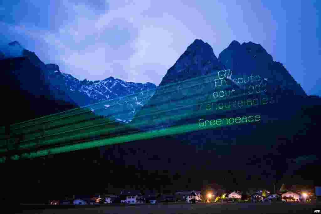 A handout photo released by Greenpeace shows a projection reading in French: 'G7 - Go for 100 percent renewables! Greenpeace' on Alps Mountains near Garmisch-Partenkirchen, southern Germany.