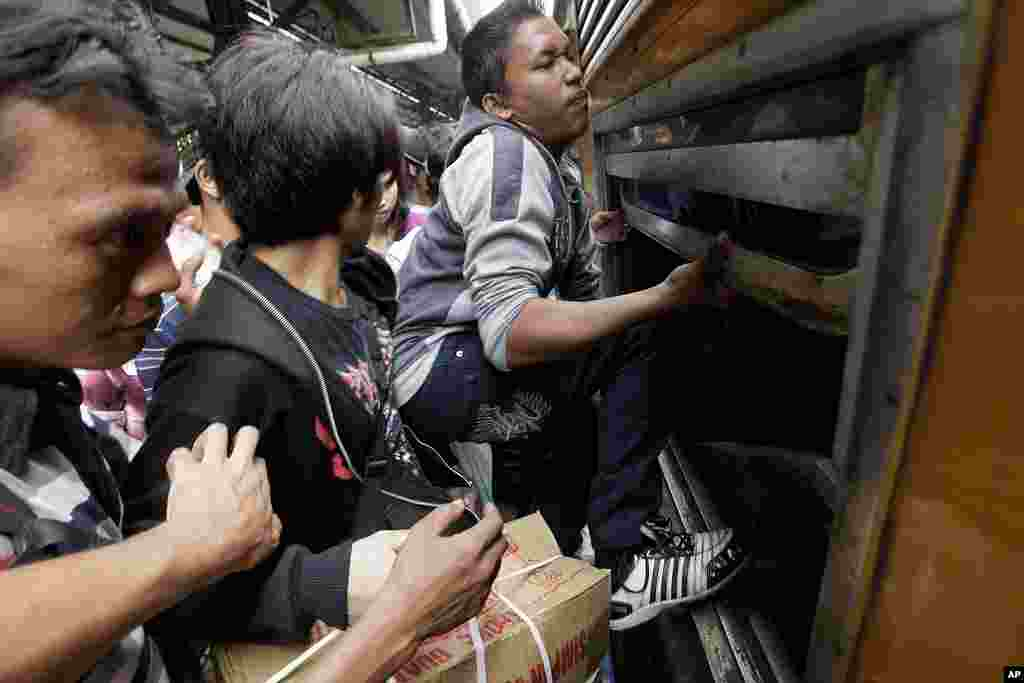 Indonesian men struggle to board a packed train through a window at Senen station in Jakarta, Indonesia, September 2010 (AP)