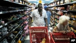FILE - Customers shop at a Harare supermarket selling goods priced in foreign currency, Dec. 8, 2008.