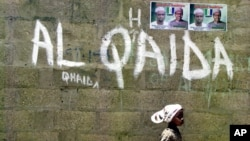 FILE - A girl walks past a wall with graffiti about the al-Qaida network in Kano, Nigeria, April 18, 2003. An airstrike this week by U.S. Africa Command targeted Al-Qaida in the Islamic Maghreb, near al-Uwaynat, Libya.