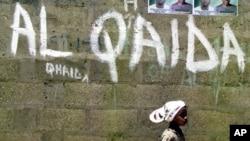 Arhiva - Devojčica prolazi pored zida na kome je grafit mreže Al Kaida, u Kanu, Nigerija, 18. aprila 2003.