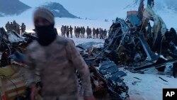 Tentara dan tim SAR berdiri di sekitar reruntuhan helikopter tentara yang jatuh di Bitlis, Turki timur, Kamis, 4 Maret 2021.