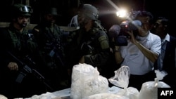 Paketi kokaina koje je kolumbijaska policija zaplenila u Puerto Gaitanu, oko 150 miles jugoistočno od Bogote