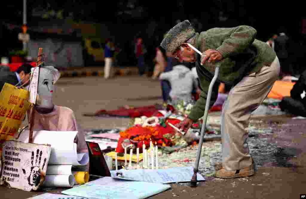 An elderly Indian man lights a candle at a makeshift memorial of a gang-rape victim in New Delhi, India, Janueary 3, 2013.