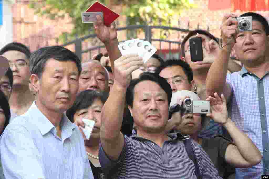 民众高举手中的中华人民共和国身份证希望能够被允许进入警戒区