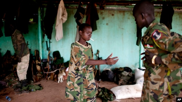 FILE - A May 2012 photo shows a young South Sudanese soldier who appeared to be drunk reaching for a lighter for his cigarette at the Sudan People's Liberation Army (SPLA) headquarters in Bentiu, Unity State.