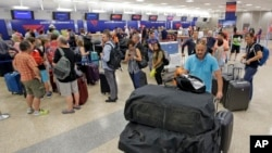 People push their bags as others stand in line after flights resumed Monday, Aug. 8, 2016, in Salt Lake City, following a computer outage. Delta Air Lines delayed or canceled hundreds of flights Monday after its computer systems crashed, stranding thousands of people on a busy travel day. (AP Photo/Rick Bowmer)