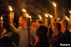 "White supremacists carry torches on the grounds of the University of Virginia, on the eve of the ""Unite the Right"" rally in Charlottesville, Va., Aug. 11, 2017."