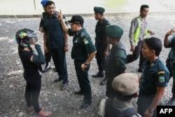 Seorang perempuan Aceh (kiri), yang sedang mengendarai motor, ditahan oleh polisi syariah karena mengenakan celana ketat tanpa hijab di Banda Aceh, ibu kota provinsi Aceh, 7 Mei 2014. (Foto: AFP)