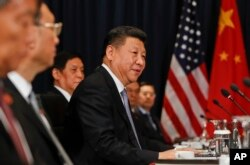 China's President Xi Jingping, center, speaks to U.S. President Barack Obama at their meeting during the Asia-Pacific Economic Cooperation in Lima, Peru, Nov. 19, 2016.