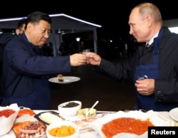 Russian President Vladimir Putin and Chinese President Xi Jinping toast during a visit to the Far East Street exhibition on the sidelines of the Eastern Economic Forum in Vladivostok, Russia September 11, 2018.