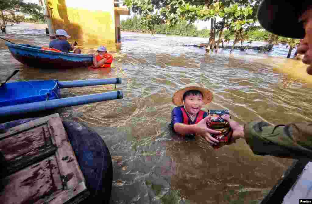 A boy gets food donation from a volunteer at a flooded area in Quang Binh province, Vietnam, Oct. 22, 2020.