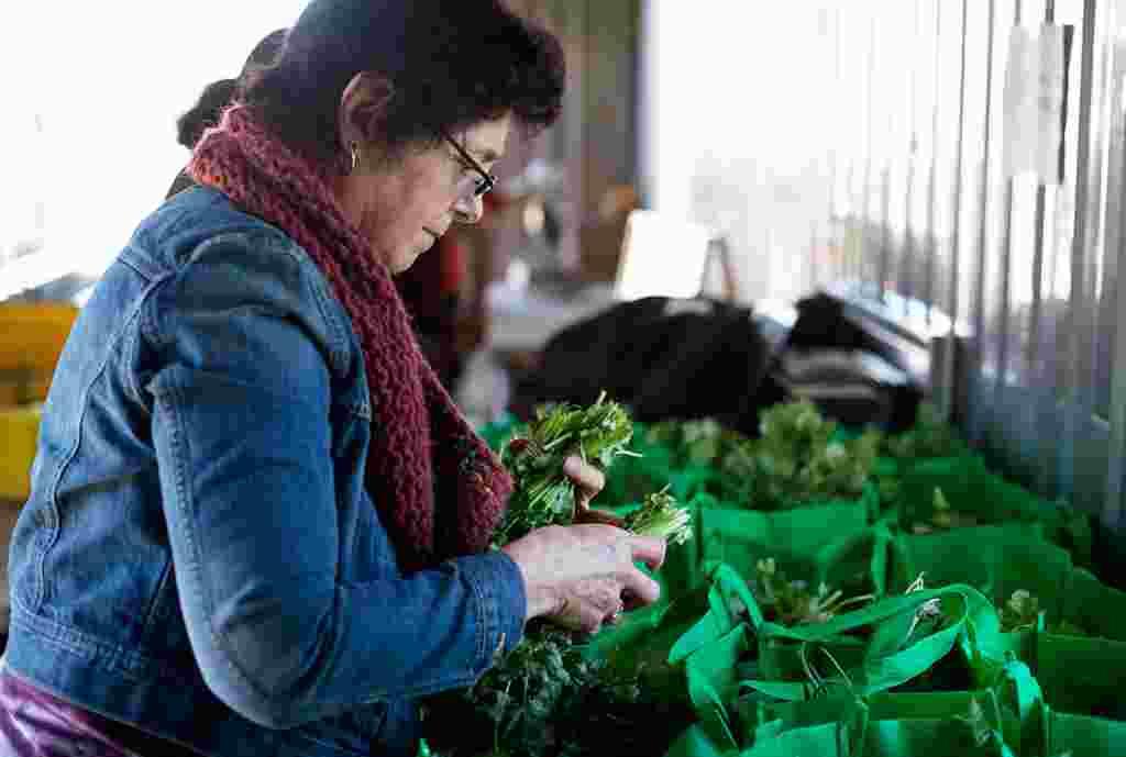 Margaret Morgan-Hubbard, fundadora EcoCity, empaca las verduras para los miembros que han comprado acciones en la cosecha de invierno.