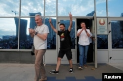 Employees of Belarusian National State TV and Radio Company leave the building and greet demonstrators during rally to protest against presidential election results.