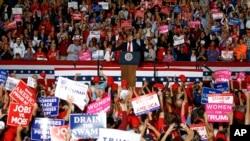美国总统特朗普2018年11月3日在佛罗里达州彭萨科拉举行的集会上发表讲话,支持者们挥舞标语。