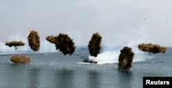 Amphibious assault vehicles of the South Korean Marine Corps throw smoke bombs during a U.S.-South Korea joint landing operation drill in Pohang, southeast of Seoul, during Foal Eagle exercises in 2013.