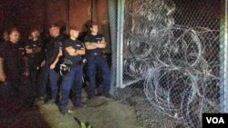Puluhan polisi dan tentara Hungaria menjaga pagar perbatasan negara mereka dengan Serbia (14/9).