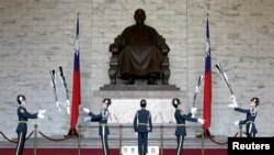 FILE - Honour guards perform in front of a statue of late Nationalist Generalissimo Chiang Kai-shek in Taipei, Feb. 7, 2007.