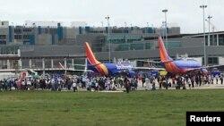 Para penumpang dievakuasi keluar dari terminal dan ke aspal pasca insiden penembakan di Bandara Fort Lauderdale-Hollywood, Florida, 6 Januari 2017. (REUTERS/Andrew Innerarity )