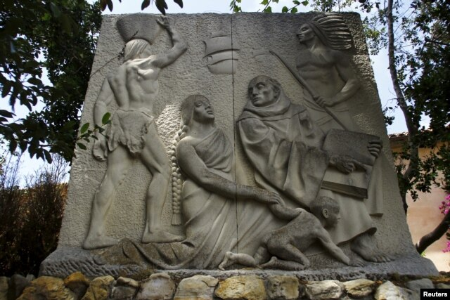 A relief sculpture depicts Father Junipero Serra with Native Americans at the Carmel Mission in Carmel, California, May 5, 2015.