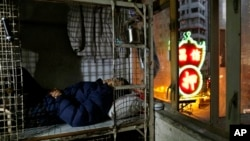 In this 2013 file photo, an elderly man sleeps in a small space he calls home in Hong Kong. The income gap in the territory has become an increasingly important issue. (AP Photo/Vincent Yu)