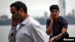 FILE - Men speak on their mobile phones on a seafront in Mumbai, Aug. 28, 2014.