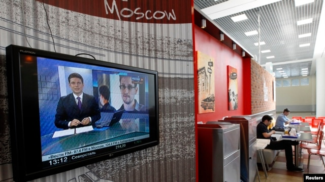 A television screen shows former U.S. spy agency contractor Edward Snowden during a news bulletin at a cafe at the Moscow's Sheremetyevo airport, Russia, June 26, 2013.