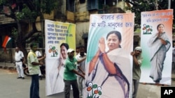 Supporters of the Trinamool Congress party, an ally to India's the ruling Congress Party, hold election billboards featuring portraits of party leader Mamata Banerjee in Kolkata, India, May 13, 2011.