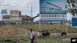 2016年11月23日肯尼亚工人坐在中国公司树立的承建铁路工程的广告牌下。