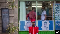 FILE - A security guard sits near a gate in Addis Ababa, Ethiopia.