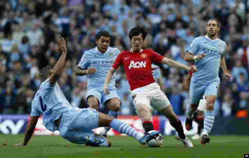Manchester City's Vincent Kompany, left, competes for the ball with Manchester United's Park Ji-Sung, third left, watched by Carlos Tevez, second left, and Pablo Zabaleta, right, during the English Premier League soccer match between Manchester City and M