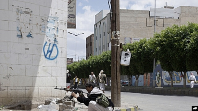 A tribesman aims his AK-47 while taking a position next to the house of Sheik Sadeq al-Ahmar, the head of the powerful Hashid tribe, during clashes with Yemeni security forces in Sana'a, Yemen, May 24, 2011.
