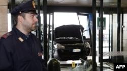Cảnh sát Ý đứng gần chiếc xe đã tông vào một trạm hành khách tại phi trường Malpesa ở Milan, thứ Hai 21/2/2011